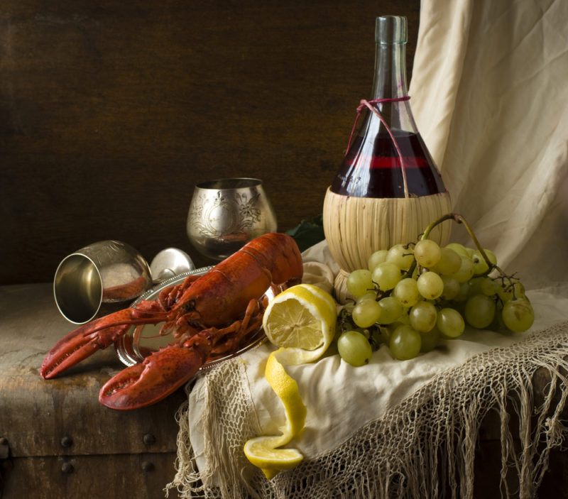 A fresh lobster on a table, with a lemon, grapes, glasses of wine, and a bottle of chianti