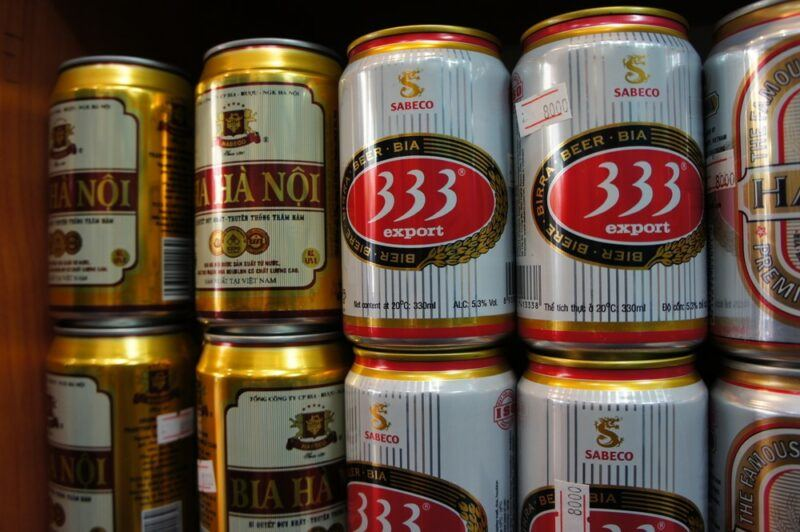 Cans of local Vietnamese beers stacked in a store