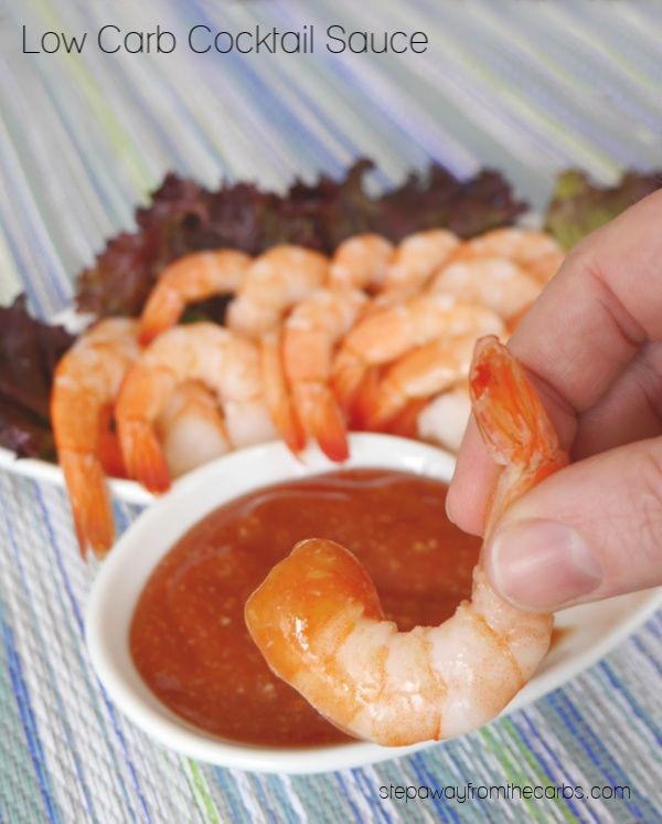 Prawns being dipped into cocktail sauce