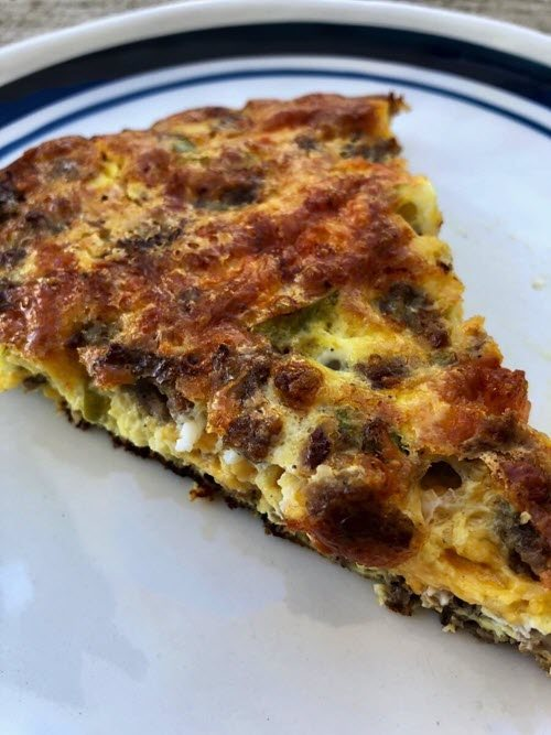 A slice of well-cooked quiche on a blue and white plate.