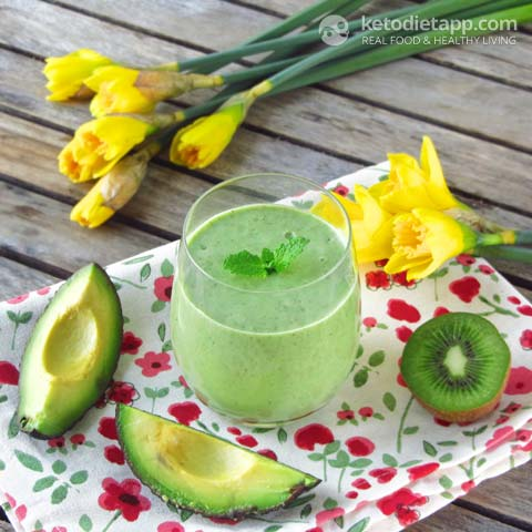 An avocado smoothie on a cloth with avocados, kiwifruit and flowers