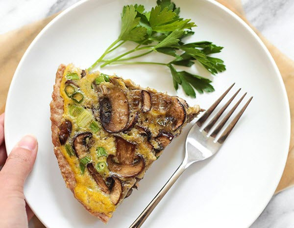 A slice of mushroom quiche on a plate with a fork.