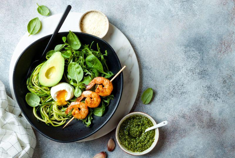 A black keto bowl with shrimp, avocado, pesto and zoodles
