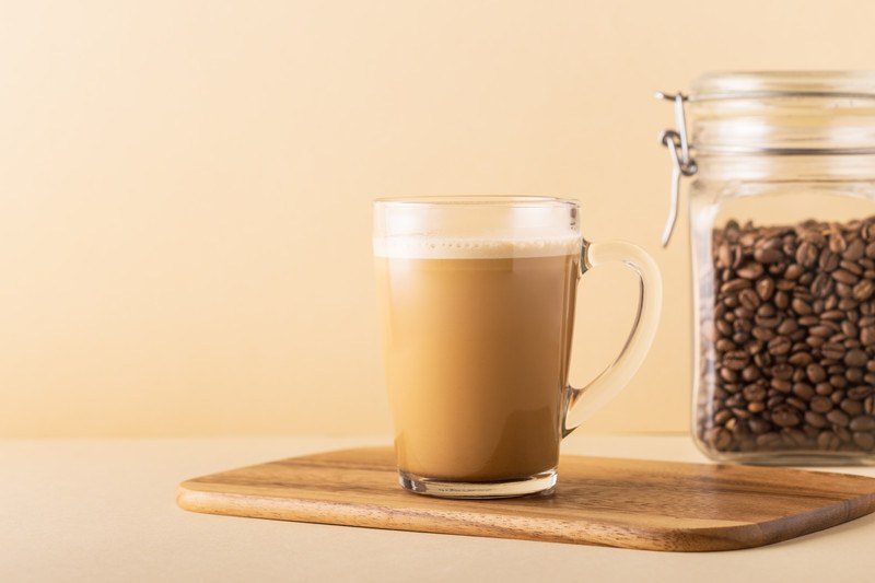 A cup of coffee blended with MCT Oil and butter rests on a cutting board near a glass canister of coffee beans.