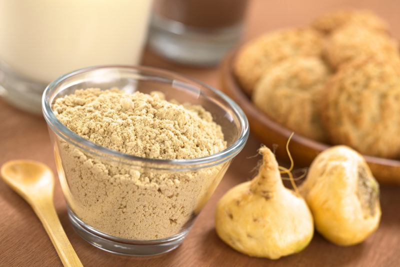 A bowl of maca powder with another bowl of maca roots in the background