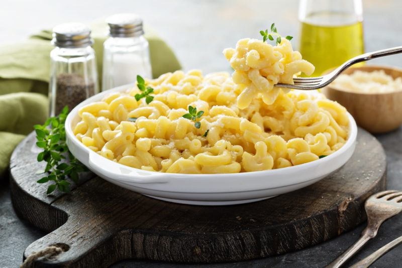 A white dish of macaroni cheese next to salt and pepper, with some being taken out on a fork