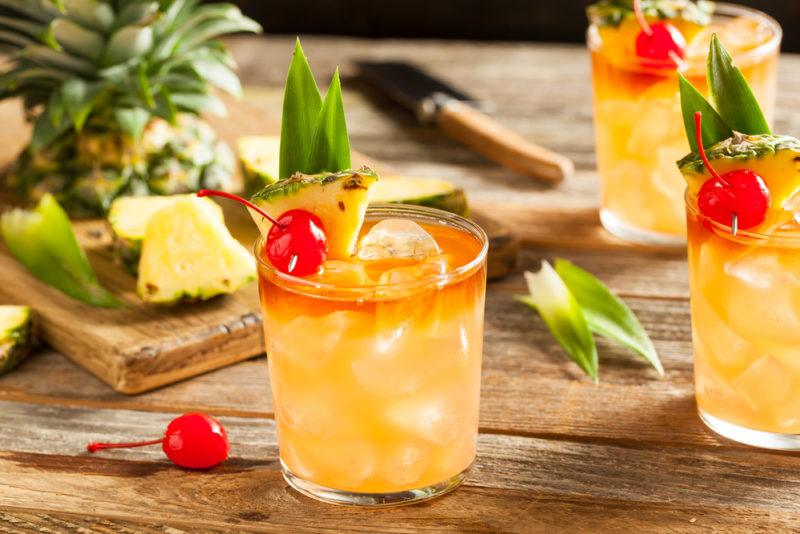 Three mai tai cocktails in short glasses with garnishes