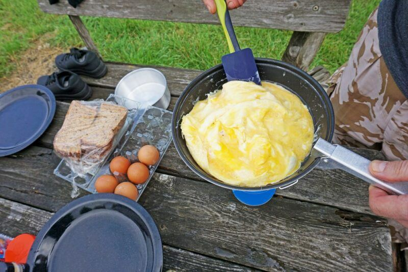 Using a frypan over a table to make an omelet, with various ingredients on the table