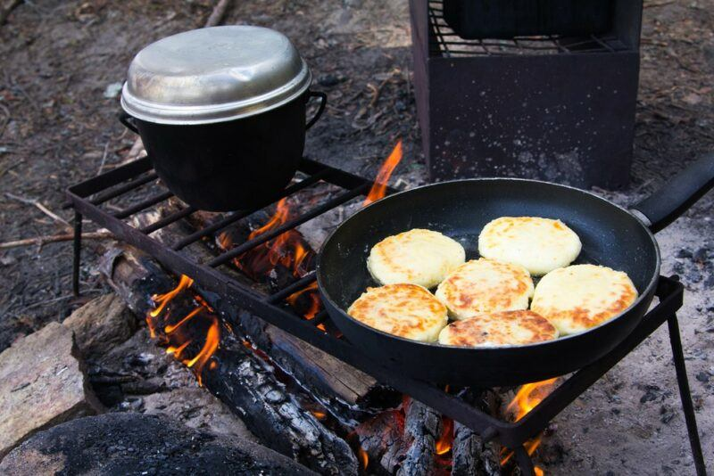Cooking a meal over a campfire using a pot, while also making pancakes in a skillet