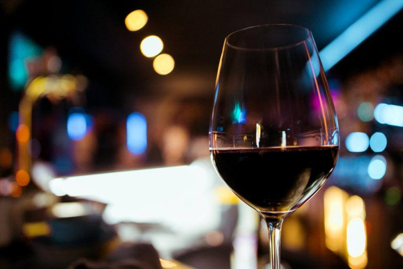 A glass of malbec wine against an out-of-focus restaurant scene