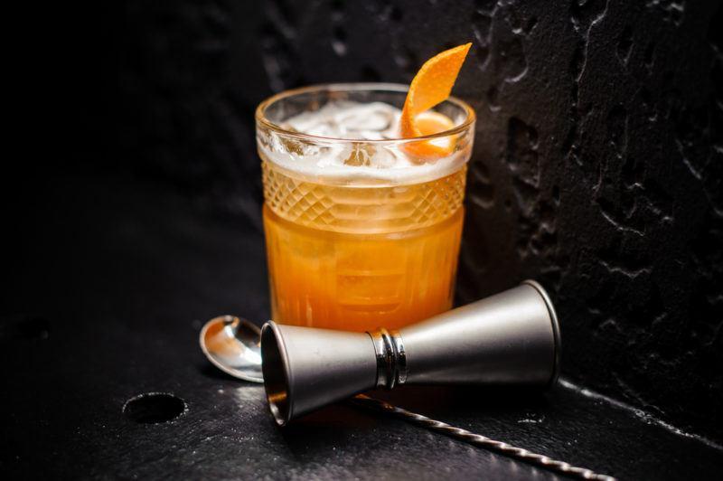 An orange Man o War cocktail next to a jigger