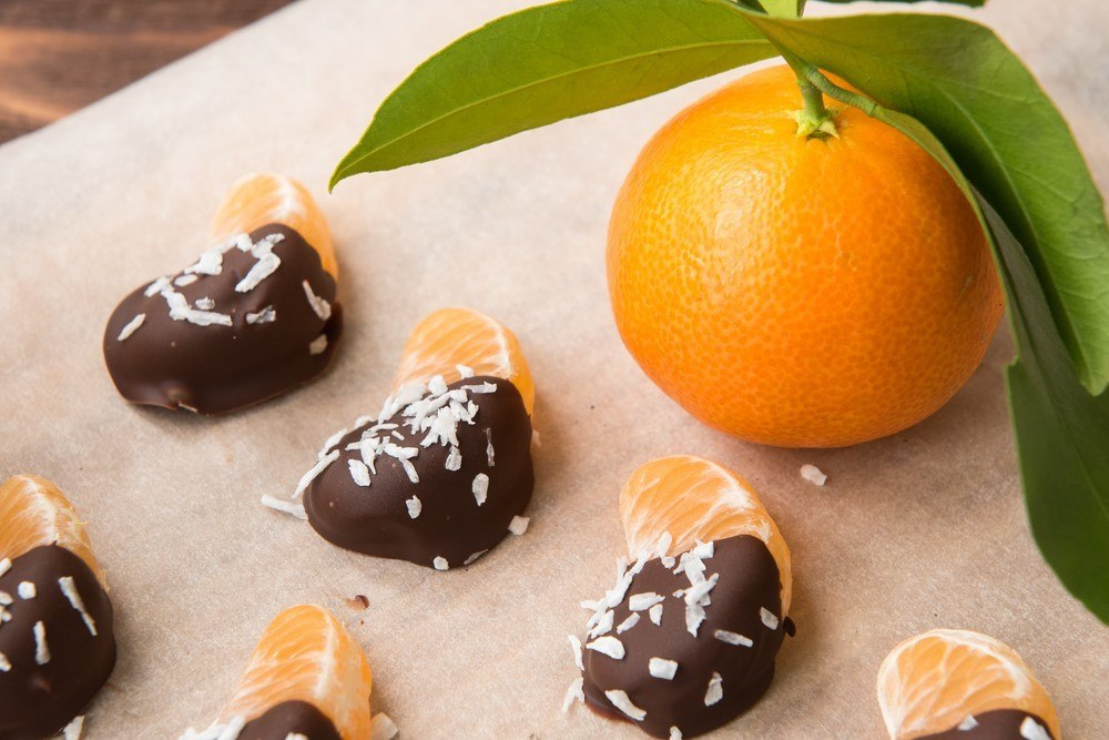 Mandarin slices on a wooden board that have been dipped in chocolate and sprinkled with coconut