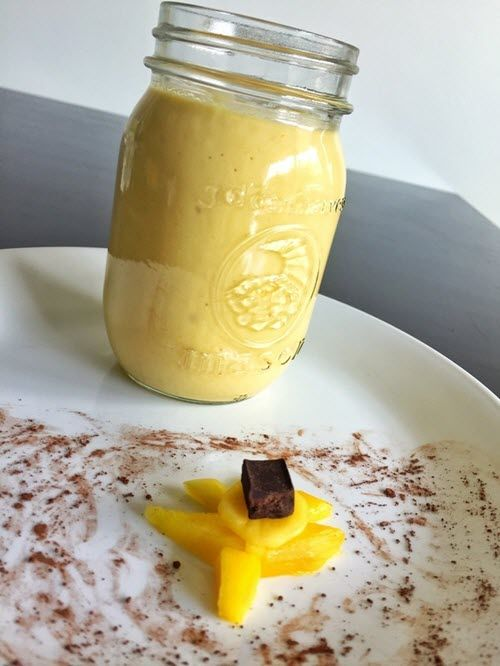A yellow smoothie on a white plate with some pieces of mango