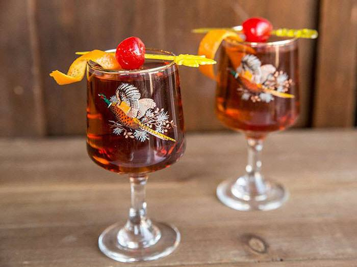 Two goblet glasses with a rum colored cocktail