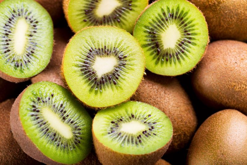 A collection of kiwis. Some of them are whole while others have been sliced in half