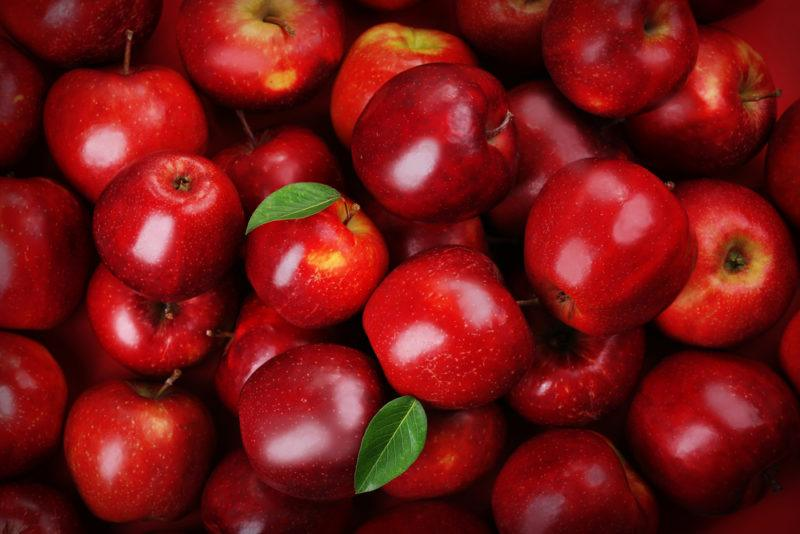 A selection of bright red apples with a few leaves all piled together