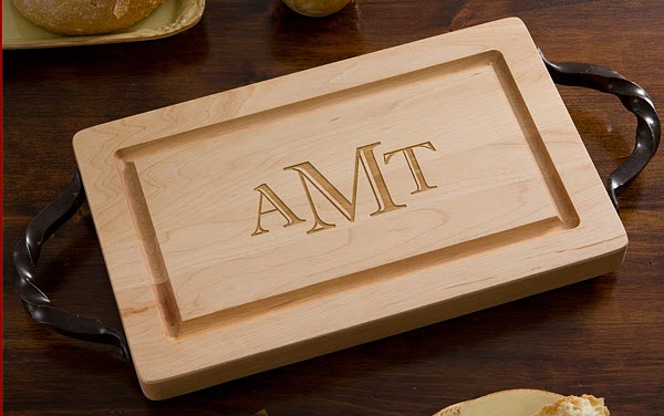 Small cutting board with black handles and three engraved letters