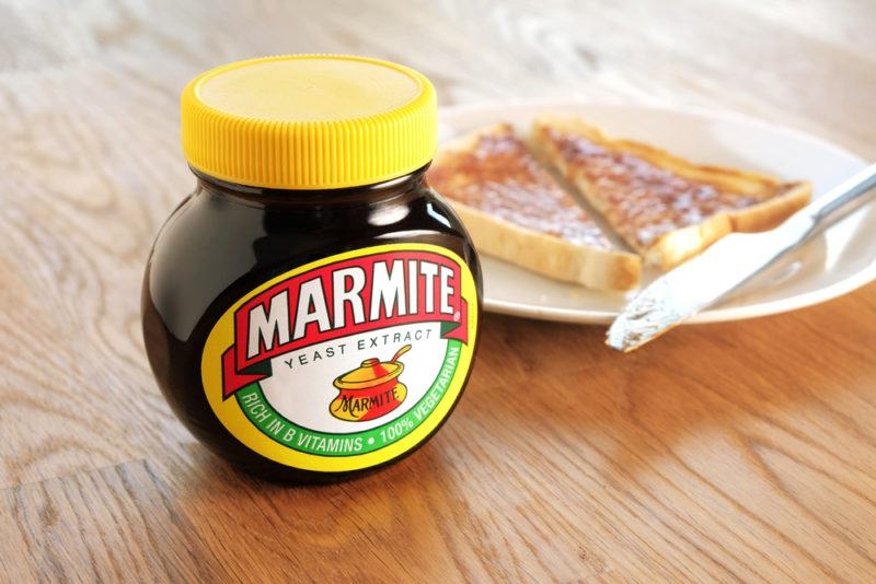 A jar of marmite with marmite on toast in the background
