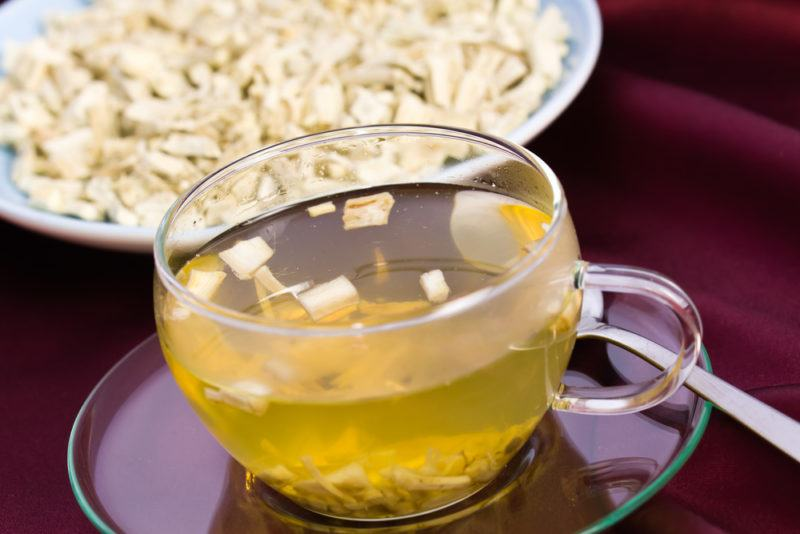 A glass mug of tea next to a bowl of marshmallow root