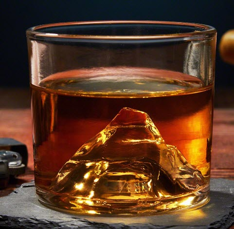 A whiskey glass with a mountain