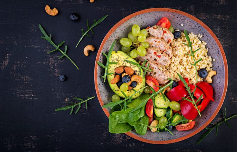 A bowl that contains bulgar, meatloaf, avocado and greens