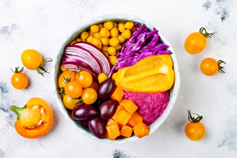 A white bowl with different purple and orange ingredients