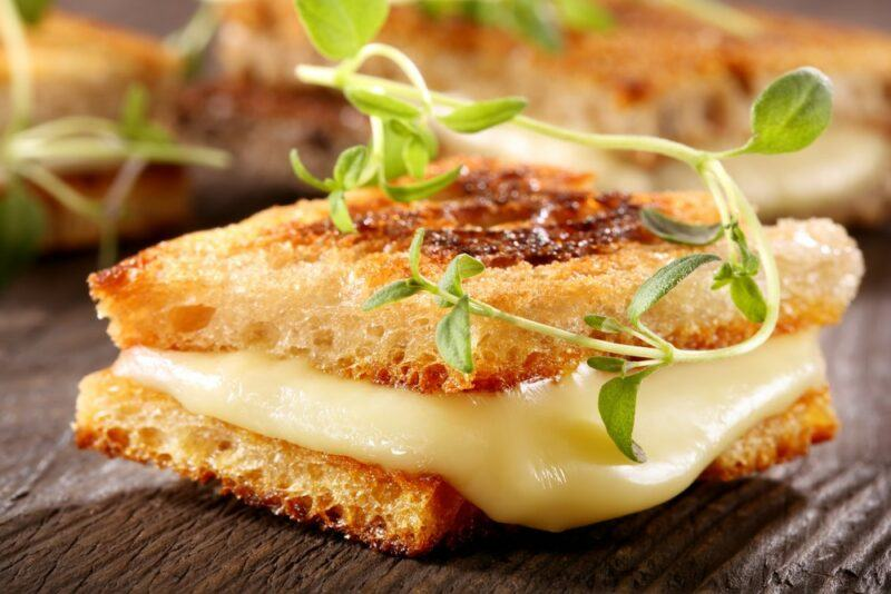 Melted cheese between two crackers with herbs
