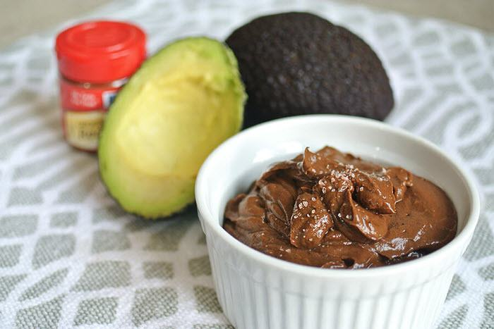 Chocolate mousse in a ramekin, with an avocado and seasoning.