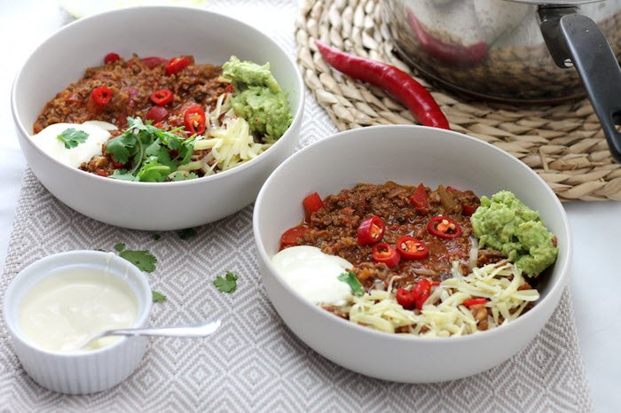 Two white bowls with chili, sour cream, cheese and guacamole