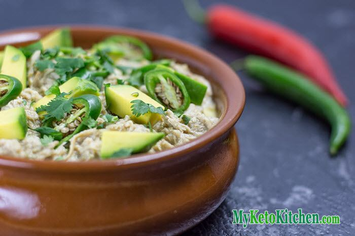A brown bowl containing chicken chili, avocados and jalapenos