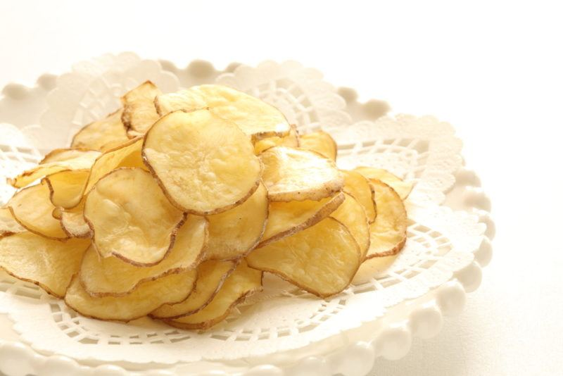 A plate of potato chips that have been cooked in the microwave