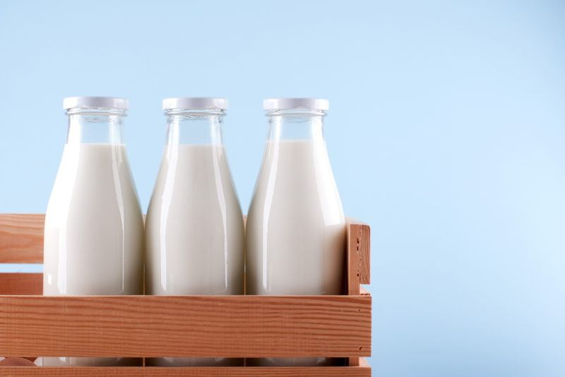 Three bottles of milk in a wooden crate