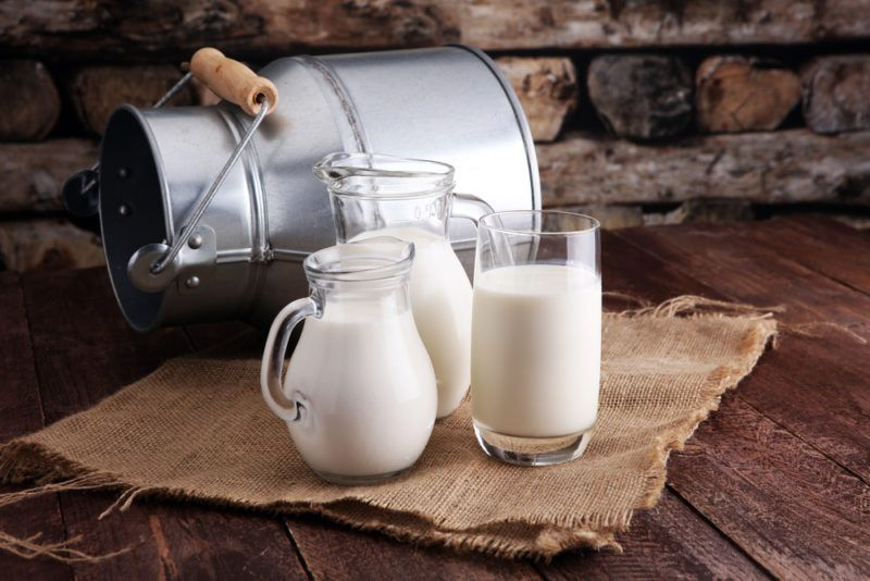 A glass and jug of milk next to a pail