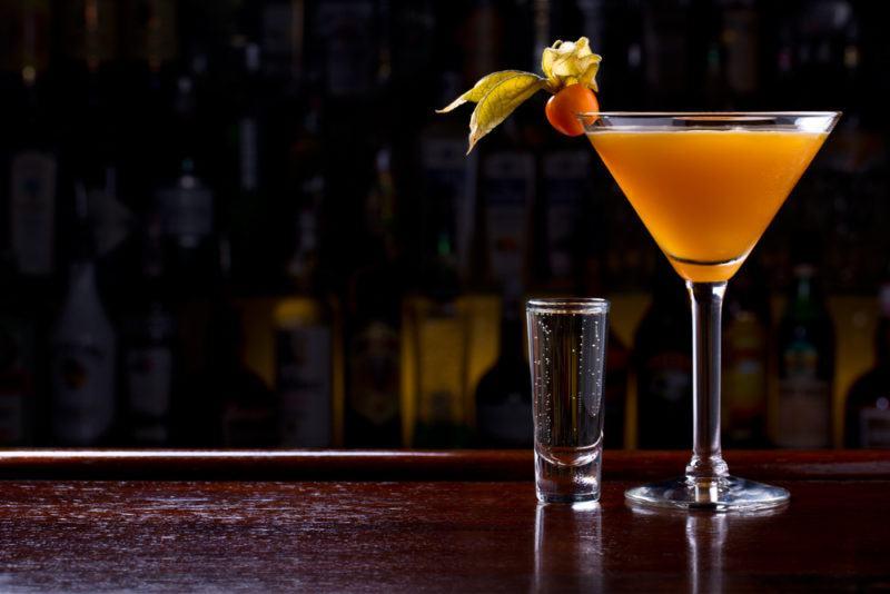 A orange millionaire cocktail in a martini glass