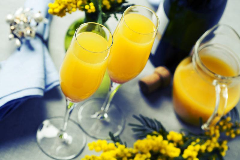 Two glasses of mimosa with a jug and flowers