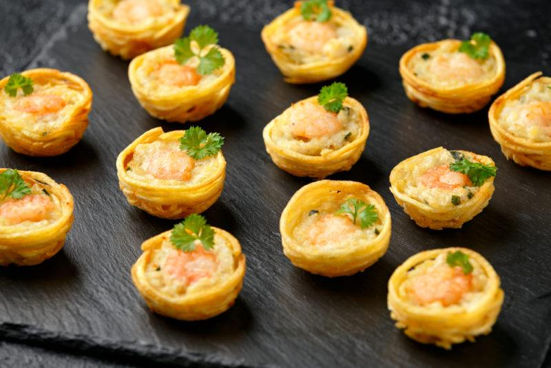 A black dish with a large number of mini fish pies
