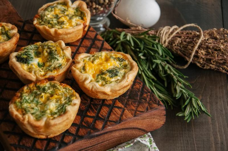 A board that contains five mini quiches next to herbs, an egg and another ingredient