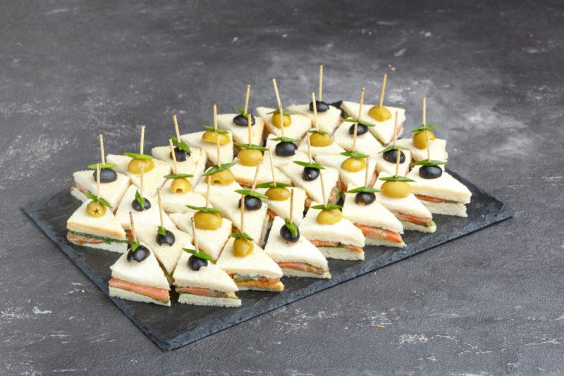 A black tray that contains mini sandwiches, each with a toothpick through it