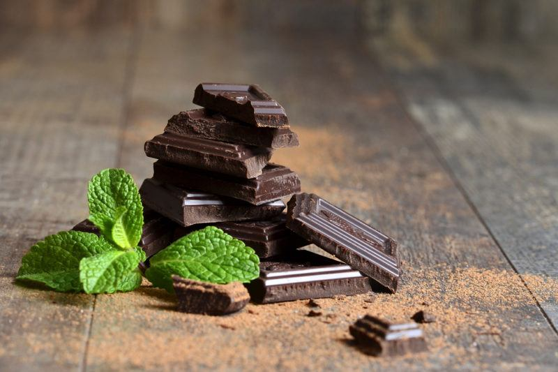 A small pile of dark chocolate next to some mint leaves on a wooden floor with chocolate powder