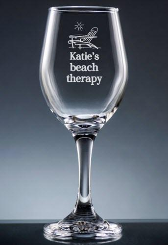 Clear wine glass with a deck chair and Katie's beach therapy engraved