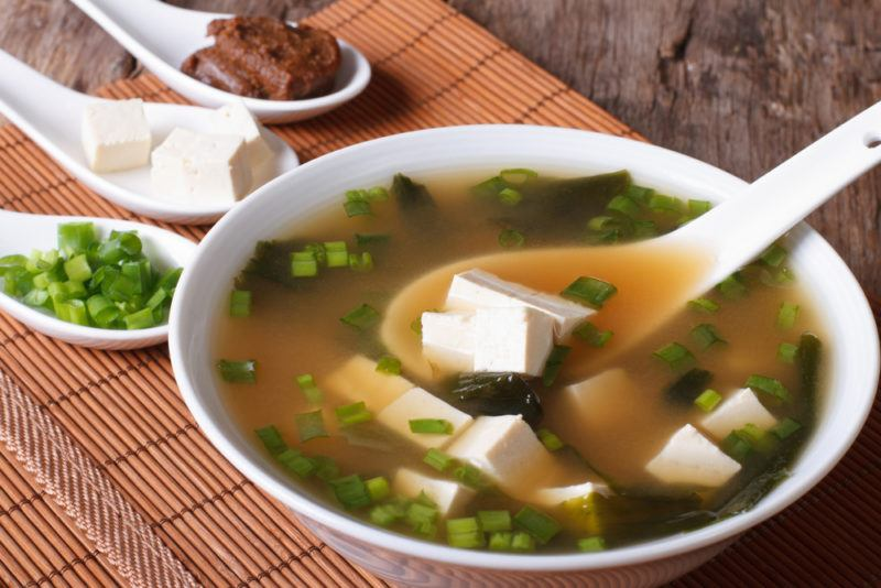 A white bowl of miso soup with tofu and a spoon