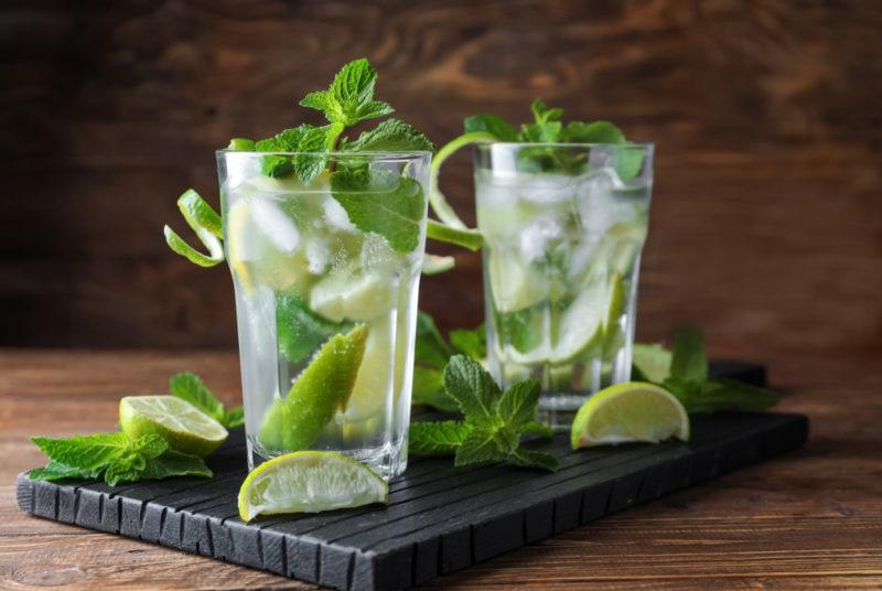 Two mojito cocktails on a board with various garnishes and other ingredients