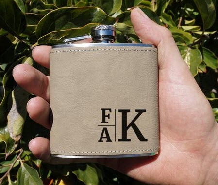 Light brown flask with 3 letters engraved into it