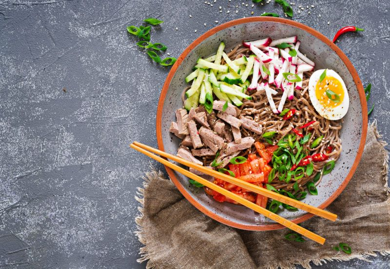 A bowl with buckwheat noodles, chopsticks and eggs