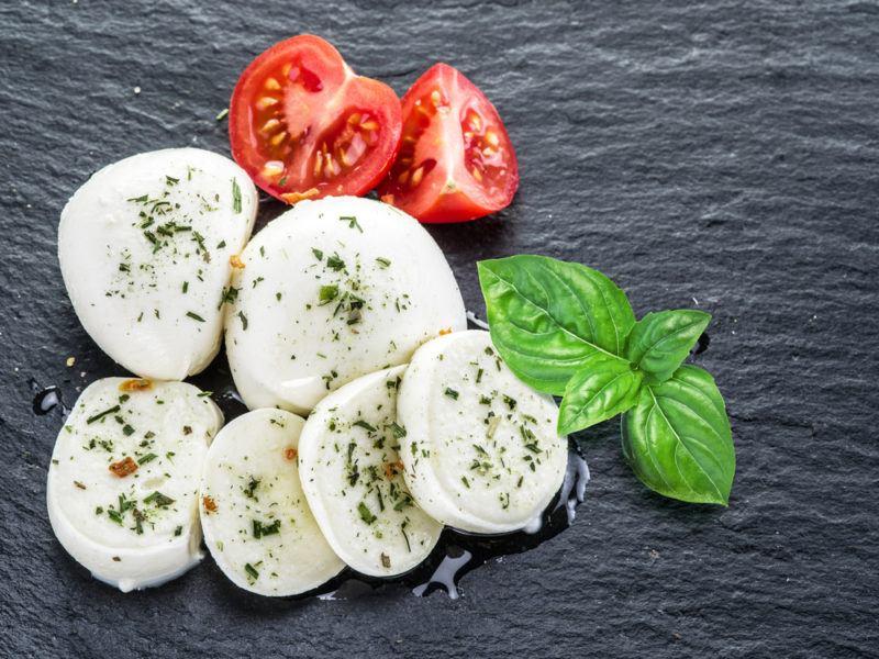 Mozzarella, basil and tomato on a gray slate background