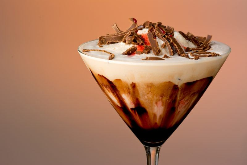 A mudslide cocktail against a colored background with chocolate sauce