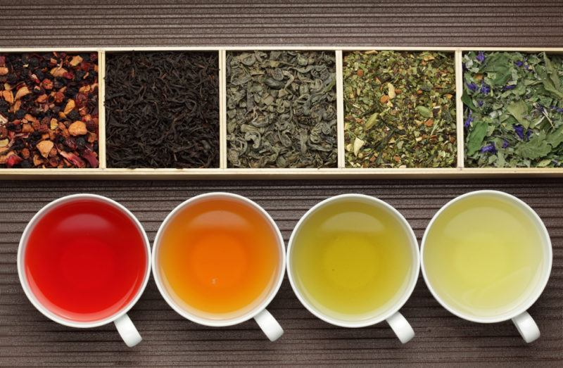 Four mugs of different colored tea and a box with five compartments, all containing different types of tea