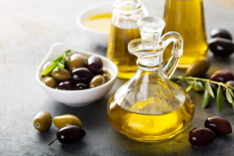 Three differently sized bottles of olive oil, with an olive brance, a dish of olive oil, and a dish of olives
