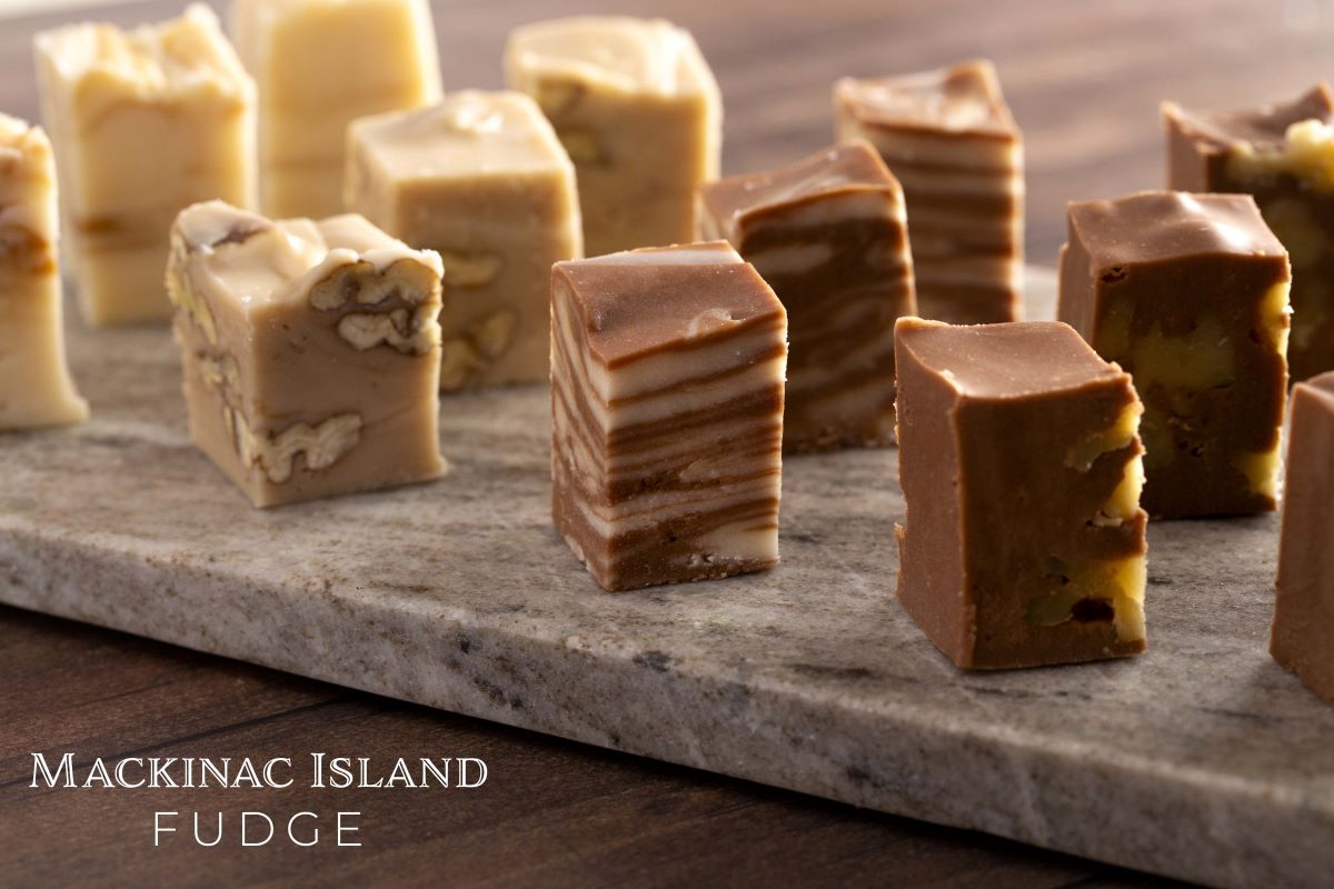 Small 2-Bite sized fudge pieces lined up on a marble tray.  From left to right, white chocolate caramel, maple and walnut, milk and white chocolate swirl, milk chocolate with walnuts.  In the lower left corner in white font it says Mackinac Island Fudge.