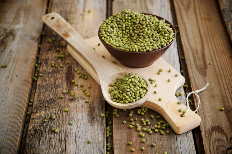 Mung beans in a wooden bowl and a spoon